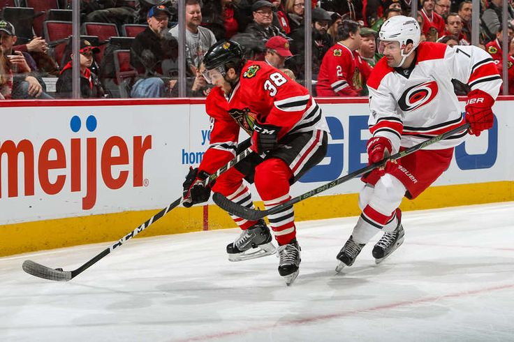 CAROLINA HURRICANES VS. CHICAGO BLACKHAWKS CHICAGO, IL - JANUARY 06: Ryan Hartman #38 of the Chicago Blackhawks and Ryan Murphy #7 of the Carolina Hurricanes chase the puck in the second period at the United Center on January 6, 2017 in Chicago, Illinois. (Photo by Chase Agnello-Dean/NHLI via Getty Images)