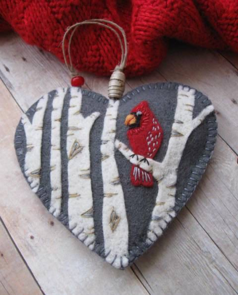 Felt cardinal ornament - i like the background color, heart shape, trees, and hanger with bead, as well as stitching around border and on cardinal. I think I'd like to see the cardinal smaller, from the side, face is a little ... ? Overall I like this though. Birch Bark Beads: Cardinal Ornament