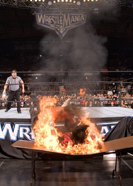 Mick finally gets his WrestleMania moment, being speared through a flaming table by Edge - WrestleMania 22