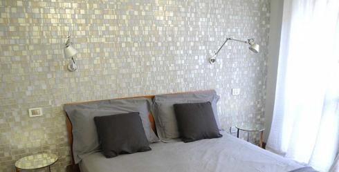 Pared de dormitorio decorada con papel pintado imitando un mosaico cerámico.