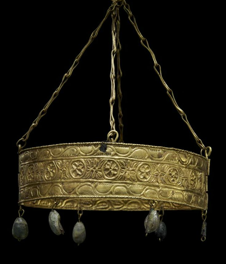 Joya que forma parte del Tesoro de Guarrazar, obra maestra de la orfebrería de la Alta Edad Media. Del Tesoro de Guarrazar se conservan un total de diez coronas, siete cruces y una incompleta y abundante pedrería. Este ejemplar pertenece al grupo de coronas de lámina repujada y consta de cadenas y diadema. De una anilla lisa cuelgan cuatro tramos de cadena de eslabones que sustentan la diadema, formada por dos semicírculos de chapa de oro.
