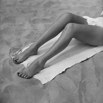 Woman Sun Tanning on Beach, Low Section Photographic Print by George Marks at Art.com
