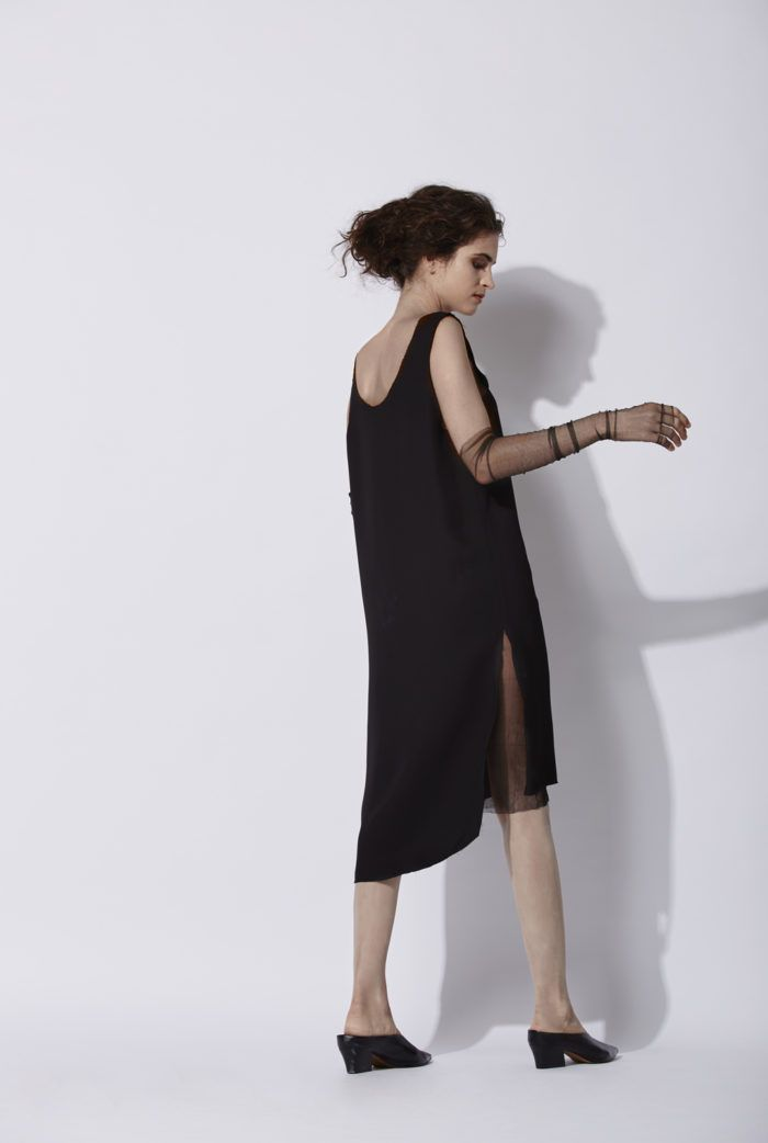 T Dress in black: Sleeveless dress with a scoop neckline. This design has two cuts on the lower sides. The finishings are frayed and the front part is shorter than the back. This model is available in black and cuire. It can be combined with a T de Tul silk tulle T-shirt underneath or a silk tulle V Dress. It can be combined with the Maga coat, which is made of the same fabric.  Made in Barcelona. Cortana AW 2016 collection. Shop online.