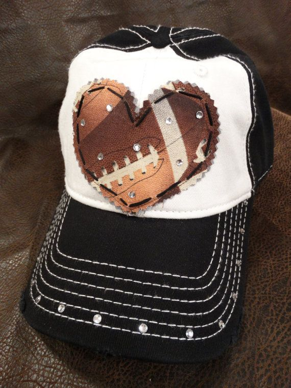 This super cute LOVE FOOTBALL cap is described:    **Two-tone (color of your choice) adjustable ball cap.  **Stitched applique football print