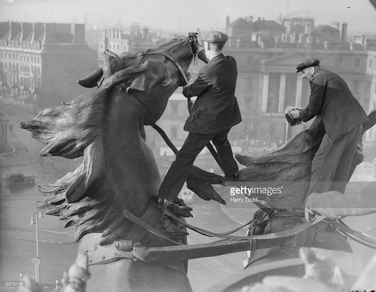 Workmen cleaning the immense statue of two horses pulling a quadriga or chariot atop the Wellington Arch on Hyde Park Corner, London, 17th January 1939.