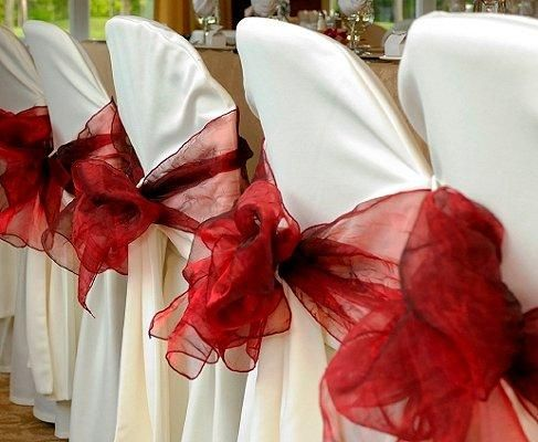 White table and chair cloths decorated with red bows and centerpieces....