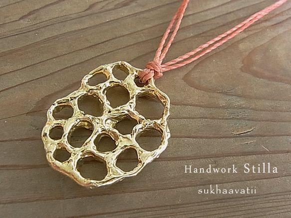 sukhaavatii シアワセアノアルトコロは蓮の実をモチーフにカタチをつくったシリーズです真鍮の蓮の実モチーフに珊瑚色の紐を2本合わせ後ろの紐を左右に引っ...|ハンドメイド、手作り、手仕事品の通販・販売・購入ならCreema。