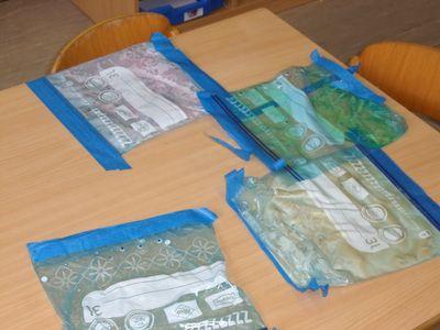 thema zakken en tassen: zakjes gevuld met haargel, zeep, lijm (er zitten ook wiebeloogjes bij)