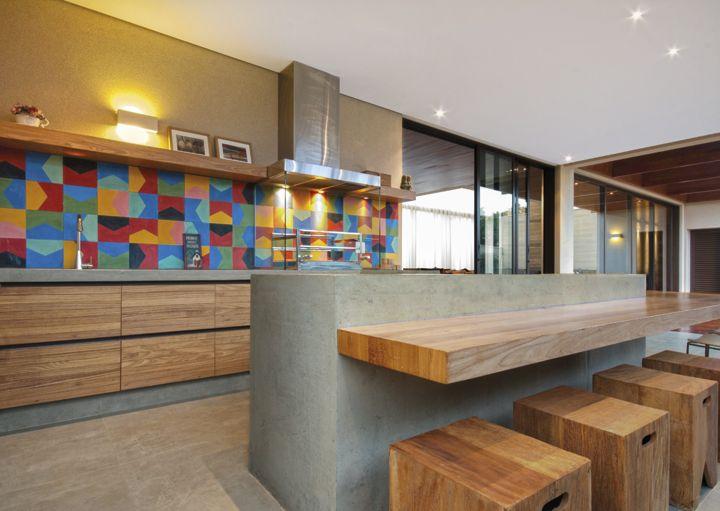 No mesmo conceito, a ilha em concreto com balcão refrigerado é abraçada por uma mesa/aparador acompanhada por banquinhos em madeira. O projeto arquitetônico é de Fernando Roma