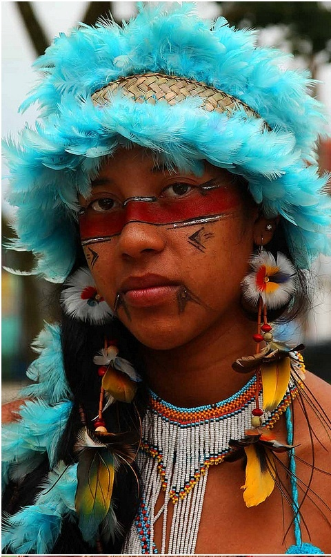 ragazza pataxò con copricapo di piume azzurre in brasile