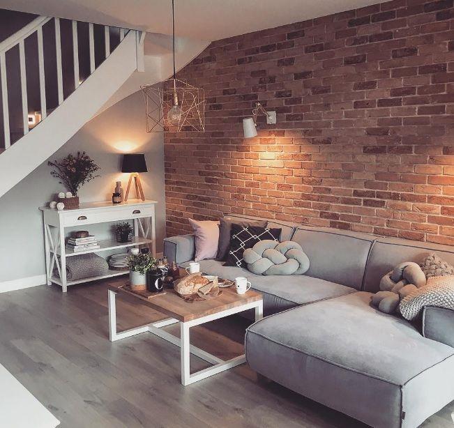 Czerwone cegły i szara sofa w salonie