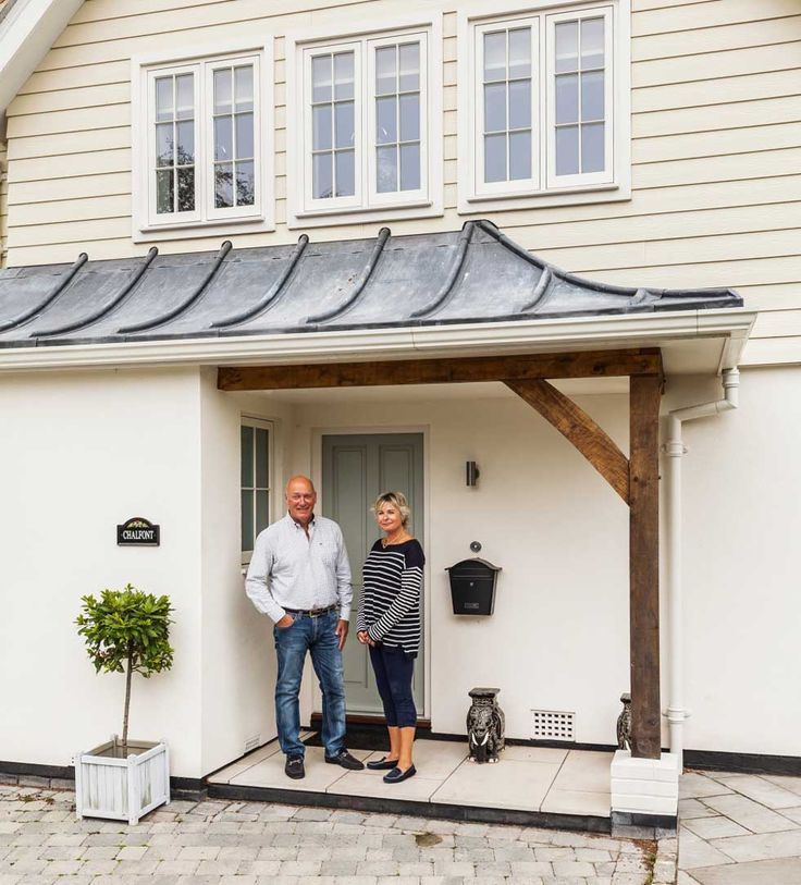 Jon and Sheila Osborne outside their remodelled New England-style house
