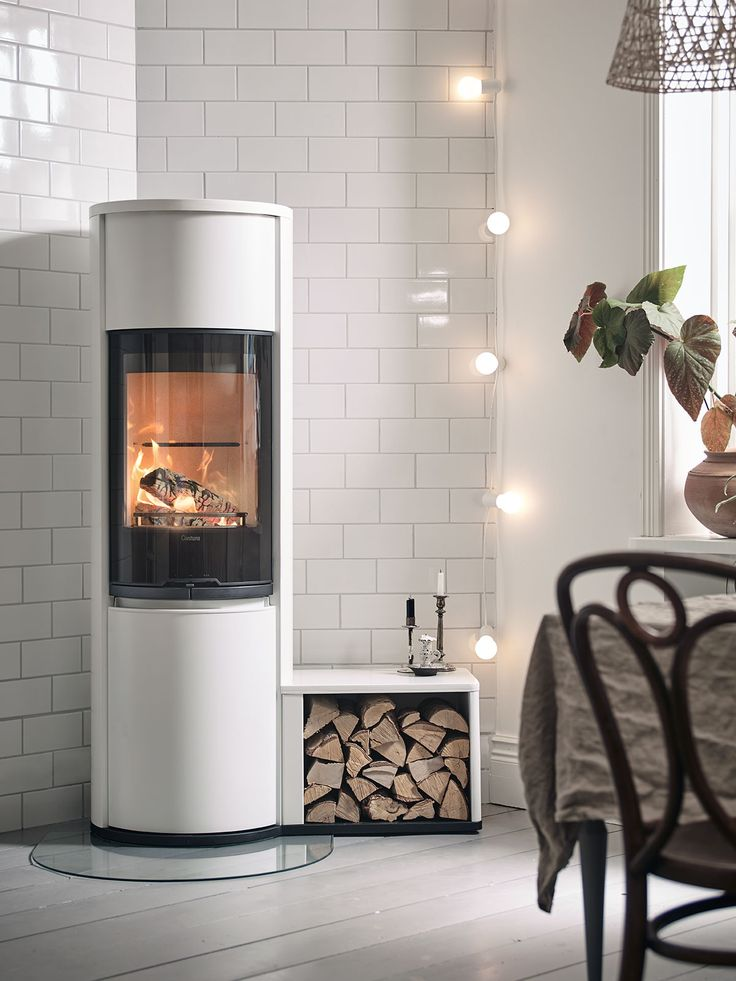 Contura 690G Style in white with glass door and a freestanding log storage.#whitestove #modernstove #modernfireplace #lightstrand #logstorage #tiledwall #nordichomes #scandininavianliving #contura600 #conturastyle