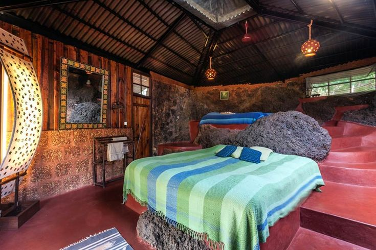 Guest rooms at Olaulim Backyards are built out of the surrounding banks, with rocks left as they are. More info: https://www.tripzuki.com/hotels/olaulim-backyards-goa/