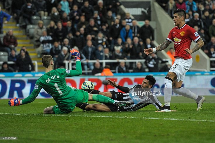 Emmanuel Riviere (C) of Newcastle slides on the ground to strike the ball whilst Goal Keeeer David De Gea of Manchester also slides in to save the shot