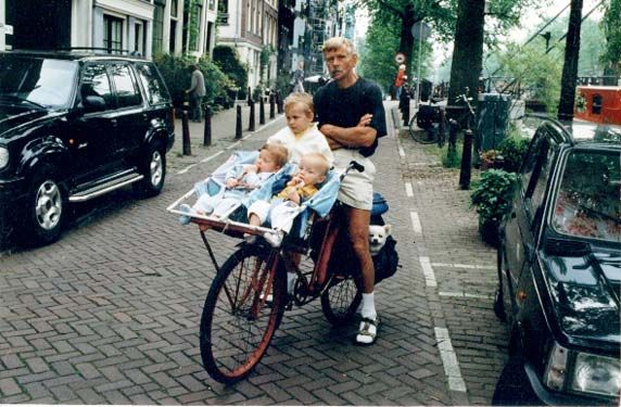 """I am 62 years old and I cycle every day 30 km. to my job in a factory, on a Racing bike with rain covers on the wheels and bags on the back. But I'll send you a picture of me and our 3 grandchildren and 2 dogs on one working bike."" ~Harry van Veen of Amsterdam, 2007"