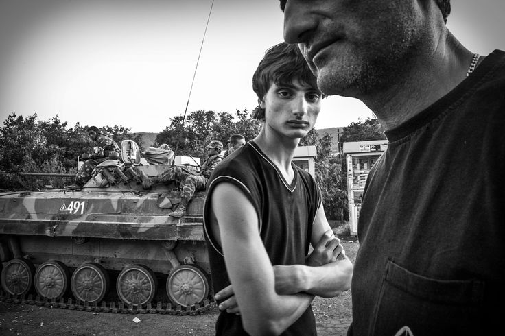 Picture of a father and son standing in front of a Russian tank blocking the highway in Igoeti