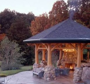 A fire pit gazebo with stone and tree accents around the columns.