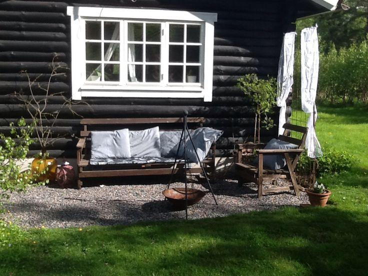 """Outdoor living!   Vår svarta timmerstuga med vita detaljer har fått en grusad uteplats med rustik look. Idag knöt jag även upp spetsgardiner på luktärternas klättervägg för att ytterligare få till """"rumskänslan""""  Love it! Cabin, gravel, rustic"""