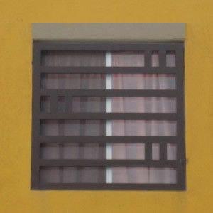 Rejas de hierro instaladas como protección de ventanas en color blanco con un diseño de herrería moderna.