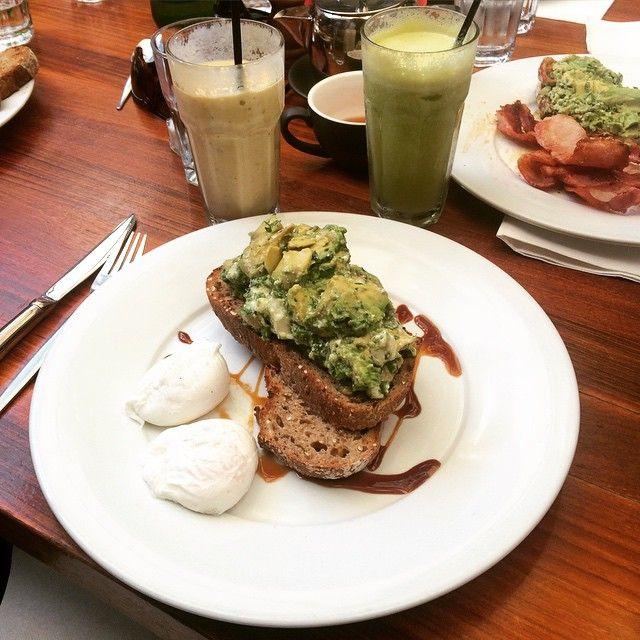 Best breakfast in Perth Australia at Vans Cafe: Avocado on toast, two poached eggs, side of bacon, and a mango passion fruit smoothie.
