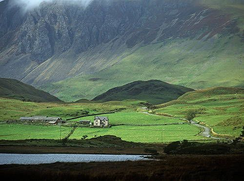 A traditional Welsh farmstead in Llyn Y Gabair,is dwarfed by the mountains of Snowdonia.