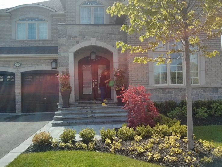 Summer urns add elegance and colour to the front of this lovely home.