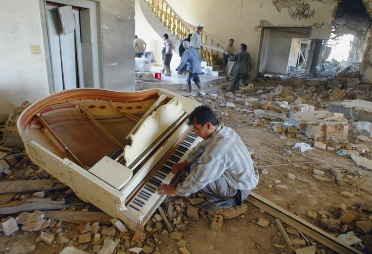 A man plays piano in one of Saddam Hussein's bombed out palaces as others loot. Bahgdad Iraq 2013 [2000 x 1371]