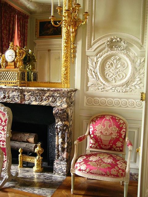 Petit Trianon – Versailles. Espejo estilo Luis XVI dorado a la hoja. Chimenea en mármol. Sillón en el mismo estilo.