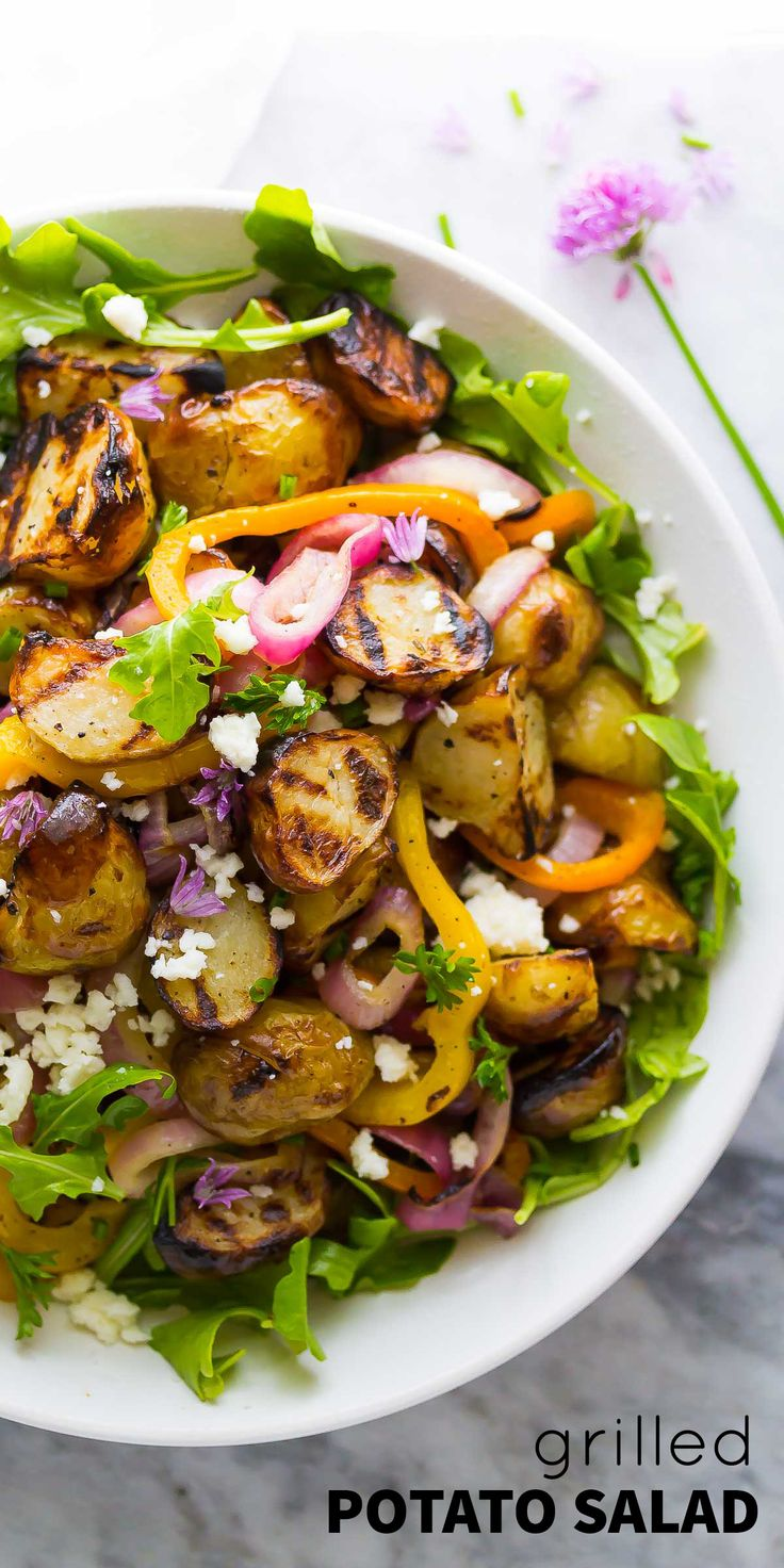 Mediterranean Grilled Potato Salad with grilled onions and peppers, feta and arugula, and tossed in a lemon-parsley vinaigrette.