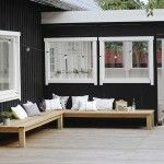 L字型に配置された木製の低いデイベッドのあるウッドデッキの屋外リビング1