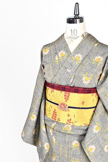 生成りと黒の糸が織り込まれた杢グレーの地に、ソレイアードのフワラーデザインを思わせるロマンチックなお花のモチーフとスクエアやストライプの幾何学パターンが織りだされたウールの単着物です。