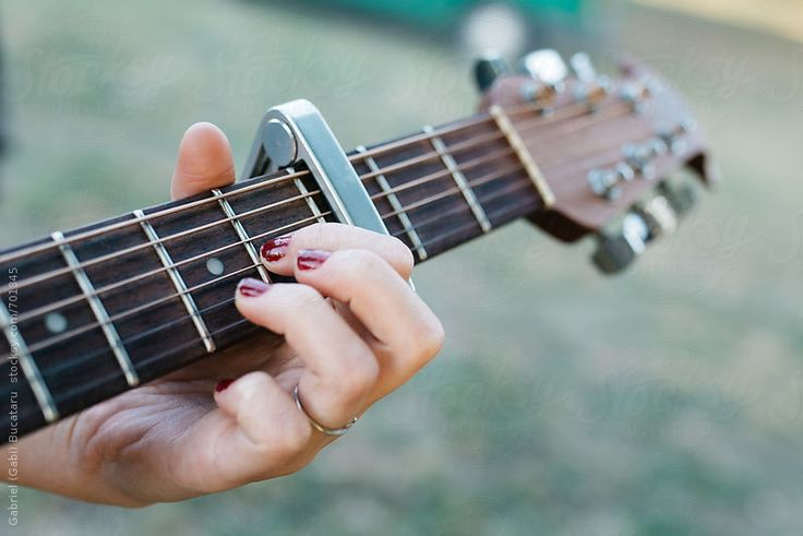 Girl's hand on an acoustic guitar
