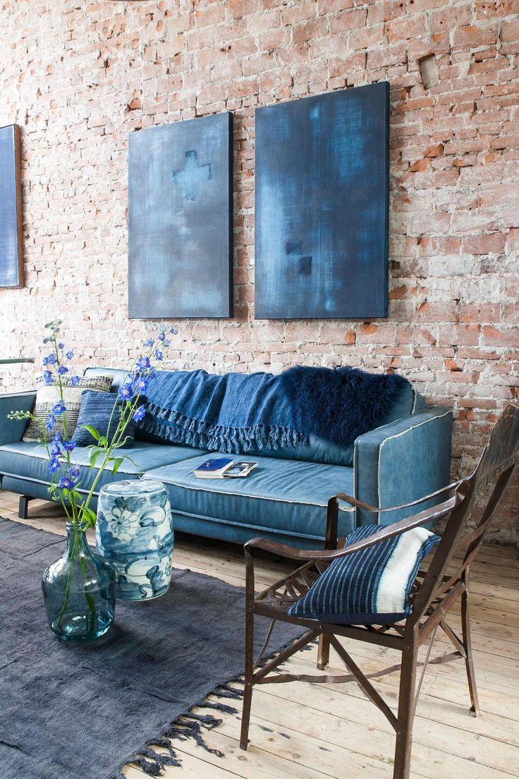 Denim Drift. Een stoere bank met jeansstof en in dezelfde stijl kunst aan de muur. Door te kiezen voor een stenen muur maak je het plaatje helemaal compleet.De kleurencombinatie is echt top!