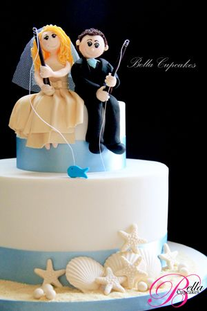"""A """"Gone Fishin'"""" spin on the beach-themed wedding cake, with a blue fish on the bride's hook (none for the poor groom haha) and blue ribbon trim, accessorized with solid white chocolate seashells. Interesting that it's only two tiers instead of the traditional three."""