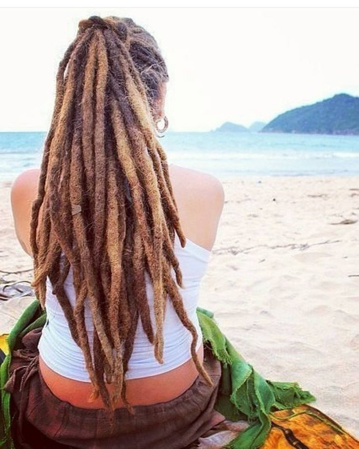 Low angle view portrait of mature man with dreadlocks against blue sky stock photo