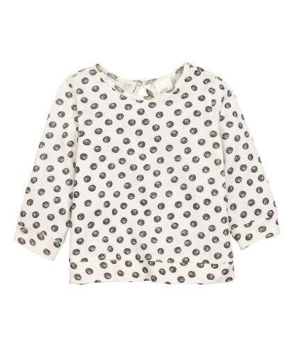 Gebroken wit/stippen. Een fijngebreide trui van zacht katoen met een print. De trui heeft een open splitje met een knoop in de nek en een boord aan de