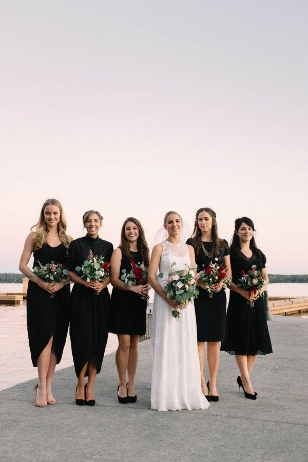 Mismatched black bridesmaid dresses and pretty pops of maroon in the leafy bouquets | Image by Micheal Beaulieu