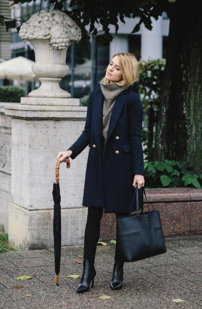 Stilvolle Frau, die den schwarzen langen Mantel-Beispiel der stilvollen Frauen-Mode-schicken Frau hält
