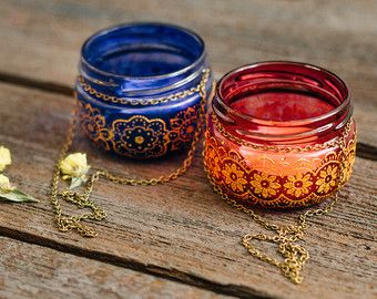 Our hanging jar candle lanterns is a gorgeous statement of the bohemian design. Inspired by the colors and smells of the Morocco evening and patterns of Indian henna, our lanterns have a story to tell.  Mix and match these tinted glass jar treasures to create patio table settings or home decor accents that speak of love, adventures, music, art and literature. Use sets of these jar lanterns and vases to create bohemian wedding decor. Our handmade lanterns make beautiful boho chic wedding…