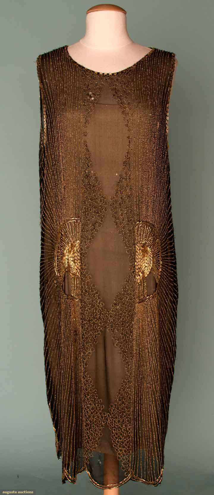GOLD BEADED PARTY DRESS, MID 1920s  Black silk chiffon, gold bead design in radiating center sun, small rings around voided diamond center shapes.