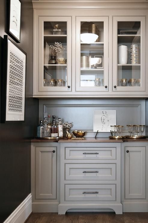 Chic kitchen pantry features gray cabinets paired with a wood countertop and a gray paneled backsplash.