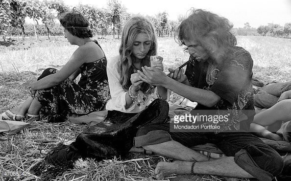 'Sitting on the grass two youngs light on a kind of pipe while a third person sits nearby her gaze lost in the grass during the first edition of the...
