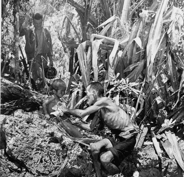 American GI watching starved, wounded man clean a small child after they emerged from caves to surrender to American troops after the defeat of the Japanese in the battle for control of Saipan. July 1944.
