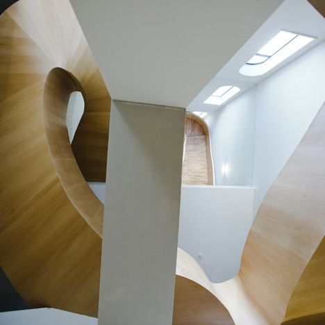 Twisting wooden staircase inside the National Olympic Committee House by Architects of Invention.