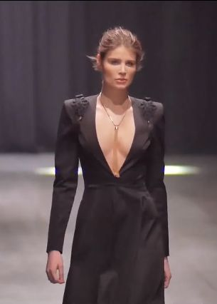 Long black dress with plunging neckline and epaulettes.