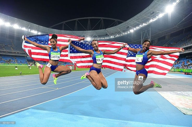 Bronze medallist USA's Kristi Castlin, gold medallist USA's Brianna Rollins and silver medallist USA's Nia Ali celebrate after the Women's 100m Hurdles Final during the athletics event at the Rio 2016 Olympic Games at the Olympic Stadium in Rio de Janeiro on August 17, 2016. / AFP / FRANCK