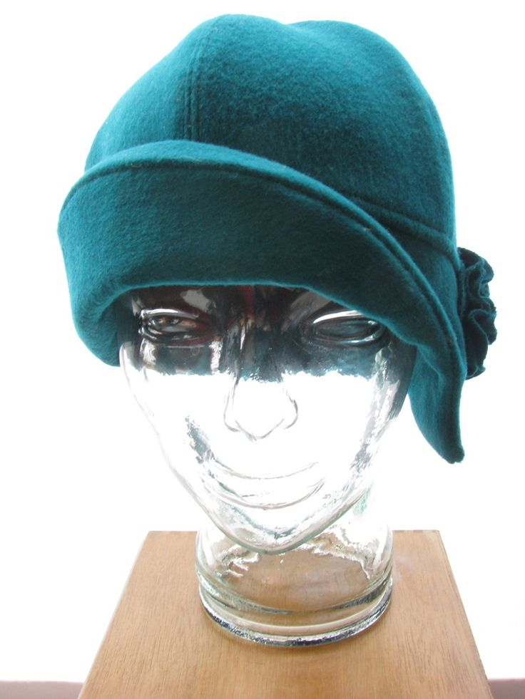 """The Stina cloche has an asymmetrical brim and a hand stitched flower detail above a face framing curl.  The brim can be worn up or down in the front and/or the back to create several looks, all echoing the charm of the 1920's. This vintage emerald green wool comes from a preloved winter coat.  Combined with a new, black micro-fleece lining, the Stina will keep you cozy and warm in the midst of any arctic cold this winter has on offer.  Comfortably fits head sizes 23 1/2""""..."""