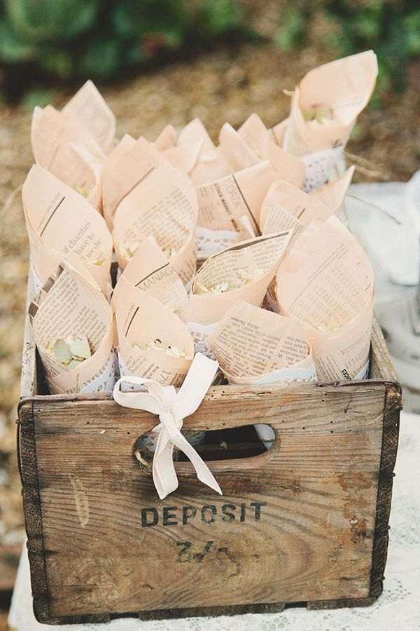 Floral confetti in wrapped newspaper cones, contained in a wooden crate