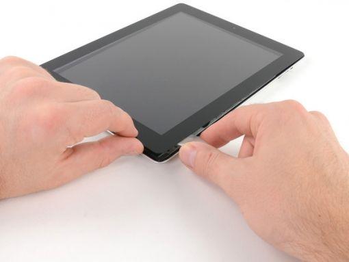Schritt 23 -      Mit einem der Plektrums heben Sie die untere rechte Ecke des iPad und nehmen Sie es zwischen die Finger.      Etwas vom Klebstoff entlang der Kanten des iPad könnte sich wieder angehaftet haben. Wenn dies geschieht, bewegen Sie das Plektrum unter die iPad-Kante, wo die Frontscheibe fest liegt, trennen Sie sie vom Kleber.